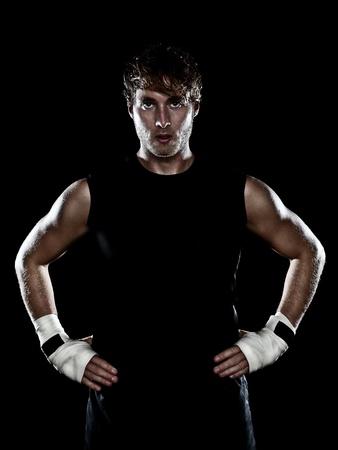 sudando: Posici�n de combate del boxeador mirando fuertes sobre fondo negro. Joven atleta masculino, cauc�sico, hombre de unos 20 a�os. Foto de archivo