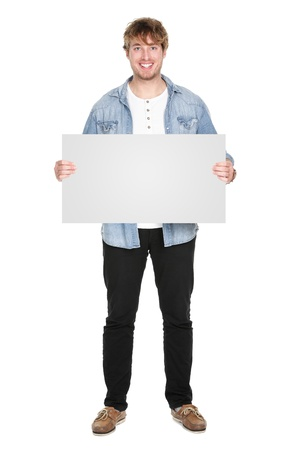 exhibiting: Man showing sign standing in full body. Casual young guy holding blank empty banner sign isolated on white background. Caucasian male model in his twenties.