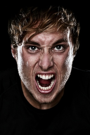 Man screaming angry aggressive at camera on black background. Young Caucasian mad male model.