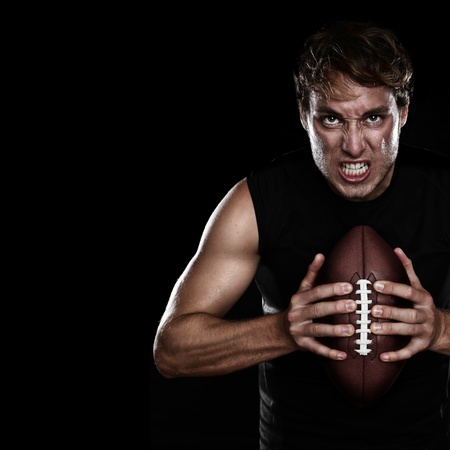 American football player staring aggressive holding american football on black background. Strong fit Caucasian fitness man with black copy space. photo