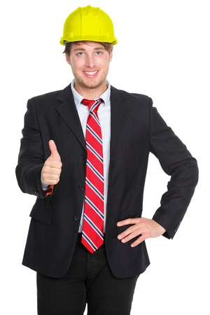 Engineer or architect showing thumbs up success hand sign in suit and construction work protection helmet hat isolated on white background. Young happy successful male professional. photo