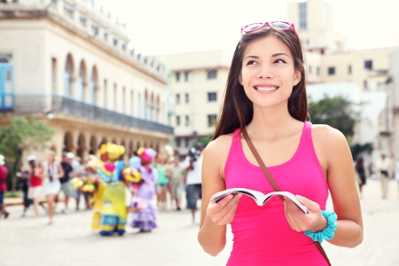 backpacking: Havana, cuba - tourist with travel guide book on Plaza de Armas, Havana, Cuba. Young woman traveler smiling happy.