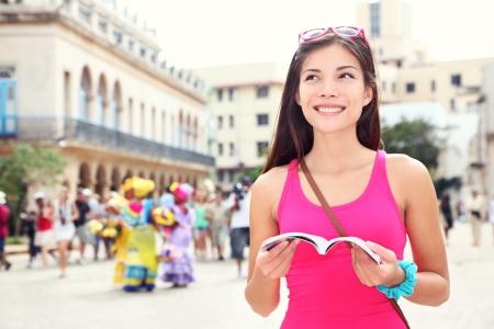 tour guide: La Habana, Cuba - tur�stica con el libro gu�a de viaje en la Plaza de Armas, La Habana, Cuba. Viajero Joven mujer sonriente feliz. Foto de archivo
