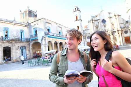 caribbeans: Tourists couple travel in Havana, Cuba having fun. Young multiracial happy couple on backpacking vaction standing on Plaza de la Catedral, Old Havana. Stock Photo