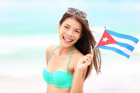 Cuba beach woman holding cuban flag during resort vacation travel on cuba. Beautiful young mixed race Asian Caucasian happy and smiling in bikini. photo