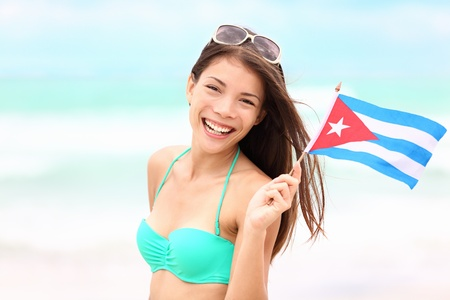 Cuba beach woman holding cuban flag during resort vacation travel on cuba. Beautiful young mixed race Asian Caucasian happy and smiling in bikini. Stock Photo - 12056440