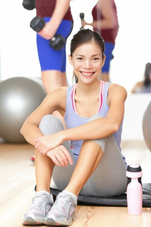 Fitness woman happy in gym smiling after training sitting taking a break on workout mat. Fit mixed race Chinese Asian  Caucasian female fitness model in gym. photo