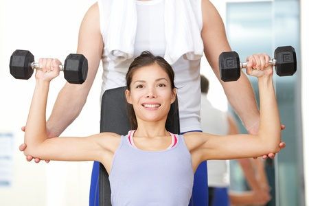 Gym fitness people - woman lifting weights with help from instructor and fitness trainer in gym. Beautiful smiling happy fit female fitness model training shoulders. photo
