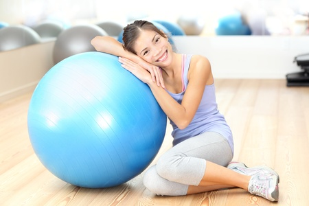 Fitness woman in gym resting on pilates ball  exercise ball after training. Beautiful multiracial fitness model in gym. photo