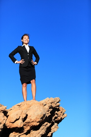 business goal: Success and challenges - business concept image. Successful business woman reaching goals overcoming challenges and adversity standing on mountain top in suit.
