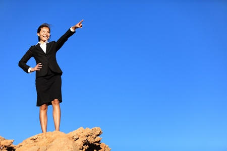 overcoming: Business concept - businesswoman pointing at future ahead standing on mountain top wearing suit.