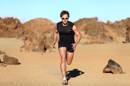 Runner running. Man sprinting in desert training for marathon. Young fit male fitness sport model working out outdoors in amazing desert landscape photo