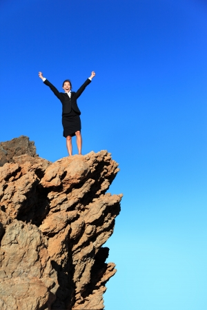 Business success concept. Businesswoman on top of mountain winning overcoming adversity and challenges. Successful young multiracial business woman in suit outdoors in nature. photo