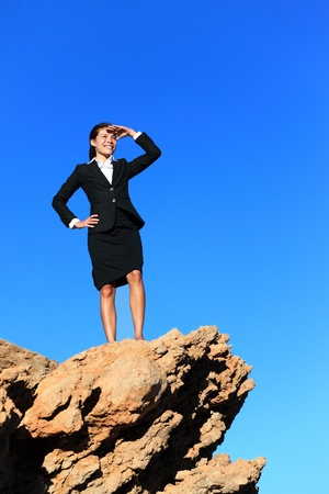 job searching: Business woman looking from mountain top. Business future concept image - businesswoman looking at horizon. Young multiracial executive.