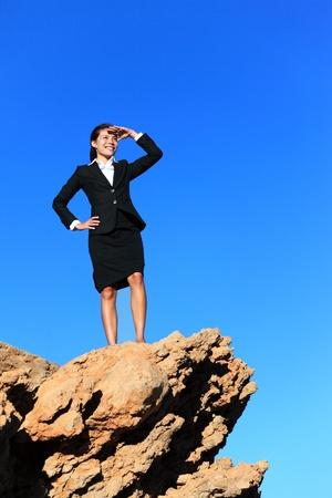 overcoming: Mujer de negocios en busca de la cima de la montaña. El futuro de negocios concepto de imagen - empresaria buscando en el horizonte. Ejecutivo multirracial joven.