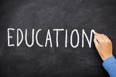 profesores: Educaci�n pizarra. Educaci�n por escrito en la pizarra. Mano que escribe con tiza en la junta escolar negro.