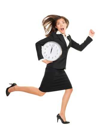 Stress - business woman running late with clock under her arm. Business concept photo with young businesswoman in a hurry running against time. Caucasian  Chinese Asian isolated on white background in full length.