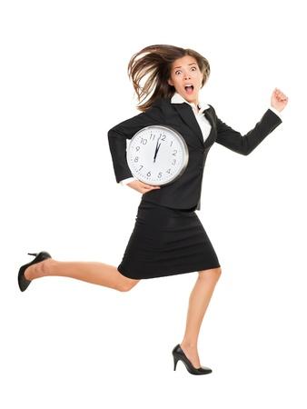 Stress - femme d'affaires en retard avec l'horloge sous le bras. Concept photo d'affaires avec jeune femme d'affaires pressé course contre le temps. Caucasien / Chinois Asiatique isolé sur fond blanc en pleine longueur.