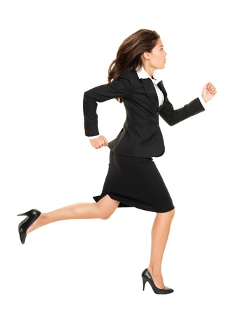 Business woman running in suit in full body isolated on white background. Business concept image with young mixed race Caucasian  Chinese Asian businesswoman. Stock Photo