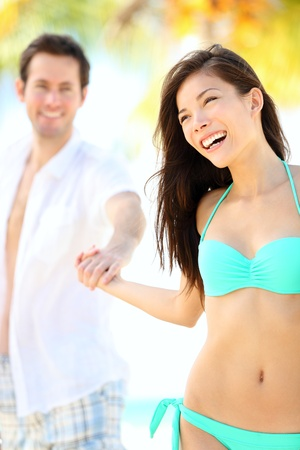beach couple having fun. Beautiful happy young couple holding hands walking on tropical beach during holidays at beach resort. Interracial couple, Asian woman and Caucasian man. From Varadero, Cuba. photo