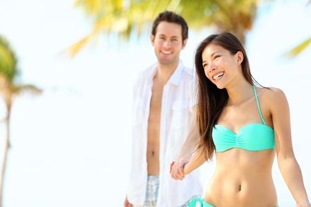 Beach vacation couple on summer holidays. Young happy interracial couple walking on tropical beach joyful holding hands. Caucasian man, Asian woman. Varadero, Cuba. photo