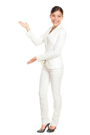 copyspace: Business woman showing and presenting something standing in white suit in full body. Mixed race Chinese Asian  Caucasian businesswoman isolated on white background.