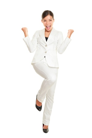Business woman celebrating happy and cheerful in white suit in full body. Cheering winner gesturing in joyful dance over success. Young multiracial Chinese Asian and Caucasian businesswoman isolated on white background. Stock Photo