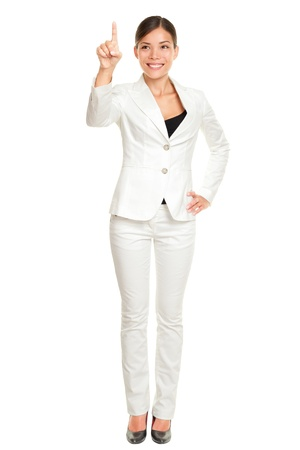 Business woman pressing invinsible button with index finger standing in full length isolated on white background. Beautiful young happy smiling multi-cultural Asian  Caucasian businesswoman. photo