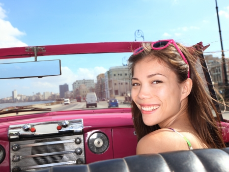 Car woman smiling happy on passenger seat in pink vintage convertible car. Young mixed race Asian  Caucasian female model during cuba vacation. Driving on Malec�n waterfront, Havana, Cuba photo