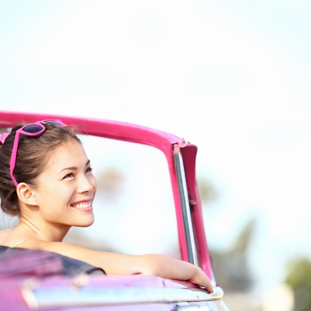 asian travel: Car woman smiling happy enjoying car road trip travel vacation. Young retro woman in pink vintage convertible car looking to side at copy space. Beautiful young multiracial caucasian  chinese asian female model. Photo from Havana, Cuba.