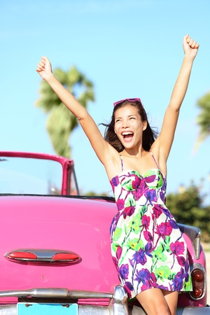 Summer vacation car road trip freedom concept. Happy woman cheering joyful in summer dress during holiday travel in pink vintage car. Beautiful young mixed race Caucasian  Chinese Asian female model in Havana, Cuba.