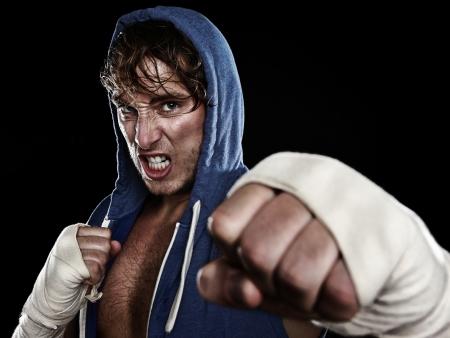 boxeador: Boxer - Street Fighter en la sudadera con capucha lucha agresiva buscando enojado con cámara de golpear con la mano envuelve la cinta en las manos. Joven modelo masculino caucásico de fitness aislados sobre fondo negro.