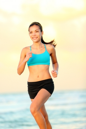women running. Female runner jogging on beach. Fit sport fitness model training for run during beautiful sunset on beach. Multicultural Asian  Caucasian fitness model in her 20s photo