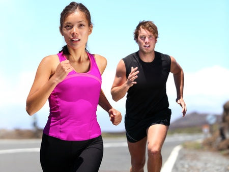 Runners - couple running training for marathon. photo