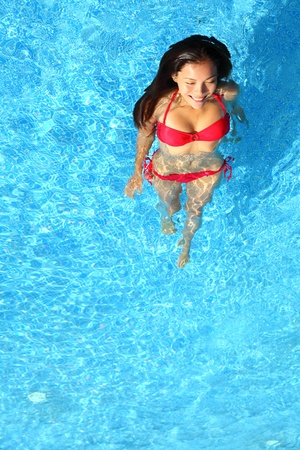 Woman relaxing in swimming pool. Beautiful gorgeous young bikini model bathing in blue swimming pool on resort during holiday. Pretty multiracial Asian  Caucasian woman in red bikini. photo