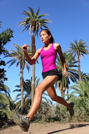 Woman running trail run at speed in tropical climate with palm trees.  photo