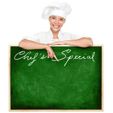 Beautiful young woman chef holding showing blank chefs special restaurant menu chalkboard isolated on white background.  photo
