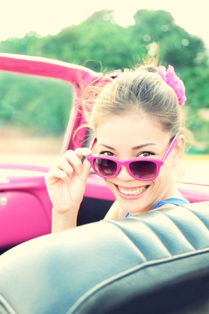 Vintage woman in pink retro car. Retro vintage processed photo of girl on road trip driving in vintage cabriolet car during summer holidays. photo