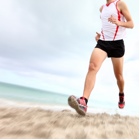 Running legs and shoes of runner jogging on beach. Caucasian sport man training for marathon. photo