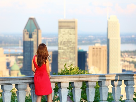 girl in red dress: Montreal. Woman looking at Montreal downtown skyline cityscape. Tourist girl in red dress on Mont Royal in spring or summer.