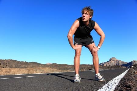 agotado: Jogger descansar después de correr. Corredor de Man tomar un descanso durante el entrenamiento al aire libre, en un paisaje fabuloso. Jóvenes de raza caucásica modelo de fitness masculino después de hacer ejercicio.
