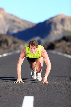 Sprinter ready for sprint. Man runner starting running sprint on road in beautiful mountain nature landscape. Fit Caucasian male fitness model during work out. photo