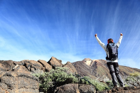 tenerife: Hiker cheering. Happy hiking woman with arms raised overcoming challenges. From hike on volcano Teide, Tenerife, Canary Islands, Spain.