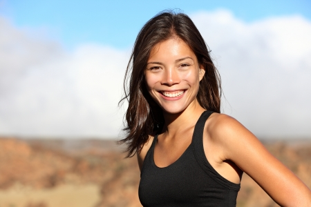 bra top: sporty outdoor mixed race woman smiling happy after workout running outside in mountain landscape. Portrait of fresh healthy multiracial Asian  Caucasian fitness model. Stock Photo