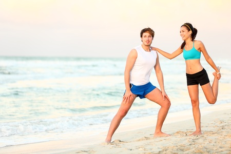 Couple doing stretching exercises workout training on beach. Young interracial running couple stretching after jogging outdoors on beautiful beach. Asian woman fitness model, Caucasian man. Stock Photo