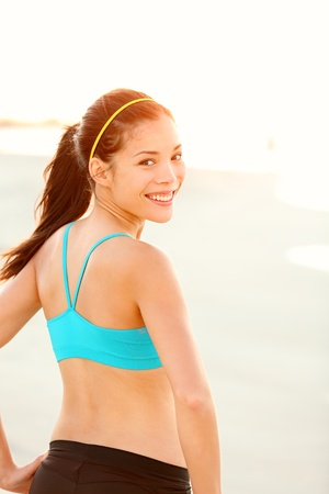 Sporty fitness woman outdoor workout. Young runner woman smiling happy resting after jogging training on beach at sunset. Beautiful mixed race Caucasian  Chinese Asian fit fitness model outside. photo