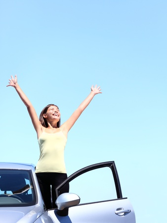 Car woman happy freedom concept. Cheering young woman with arms raised stepping out of new car under blue sky. Beautiful young multiracial Asian  Caucasian female model free. photo