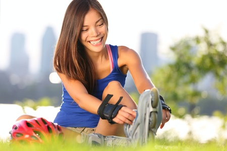 rollerblade: Roller skating woman putting on inline skates for rollerblading. Healthy outdoor workout woman skating outside with montreal city skyline in background. Stock Photo