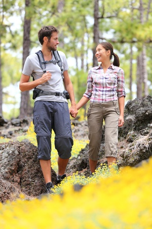 Hiking couple walking in forest. photo