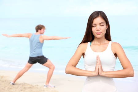Yoga meditation couple meditating outdoor on beach.  photo